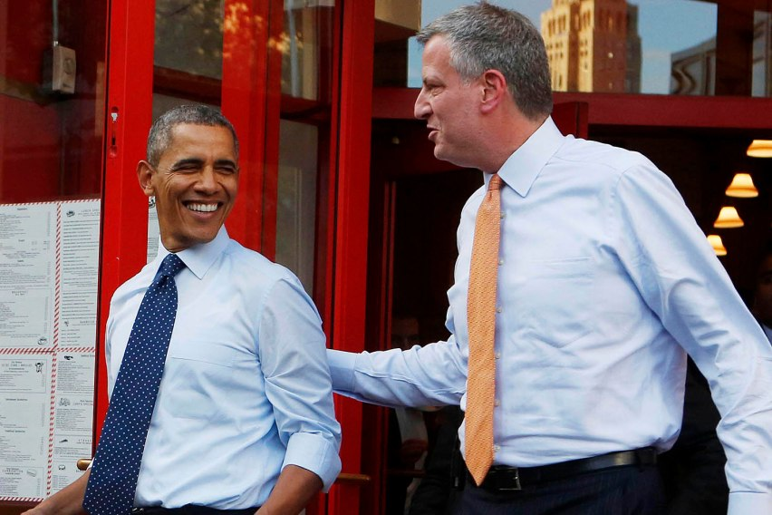 U.S. President Barack Obama walks out with two bags of cheesecake from Junior's Restaurant next to Democratic Mayoral candidate Bill de Blasio in Brooklyn