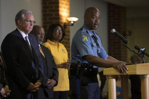 Highway Patrol Captain Johnson speaks, as Missouri Governor Nixon watches, during a news conference at University of Missouri-St. Louis in St. Louis