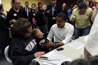 (HR) ABOVE: Senator Barack Obama takes young 13 month old Gracie McCormick into his arms as proud mother Colleen looks on. Senator Barack Obama made a surprise visit to the Campaign for Change office in Brighton and helped volunteers make phone calls to v