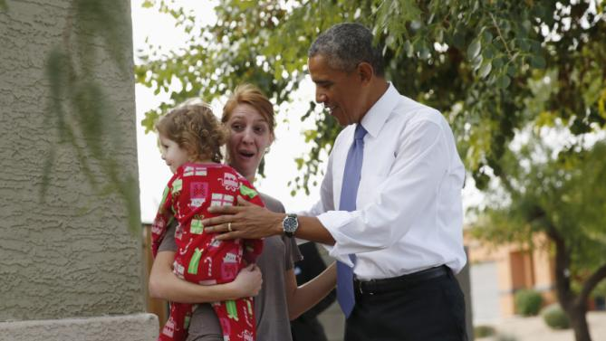 U.S. President Barack Obama greets a woman and child during a visit to a Phoenix neighborhood