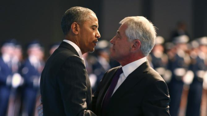 U.S. President Barack Obama hugs outgoing Defense Secretary Chuck Hagel during a farewell ceremony at Joint Base Myer-Henderson Hall in Virginia,