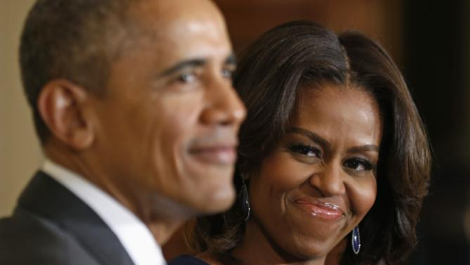 """First lady Michelle Obama smiles at U.S. President Barack Obama during the announcement of the  """"Let Girls Learn"""" initiative at the White House in Washington"""