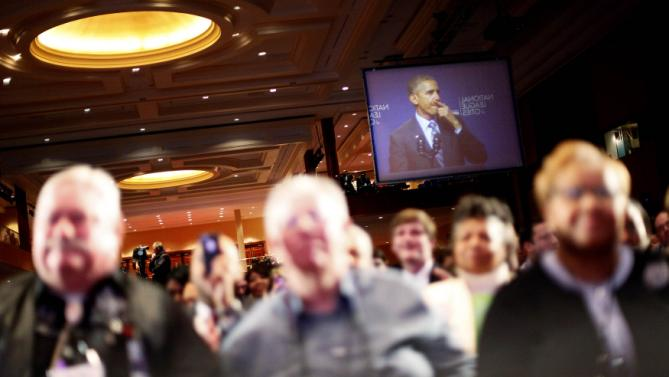 Obama appears on a video screen as he addresses the National League of Cities annual Congressional City Conference in Washington
