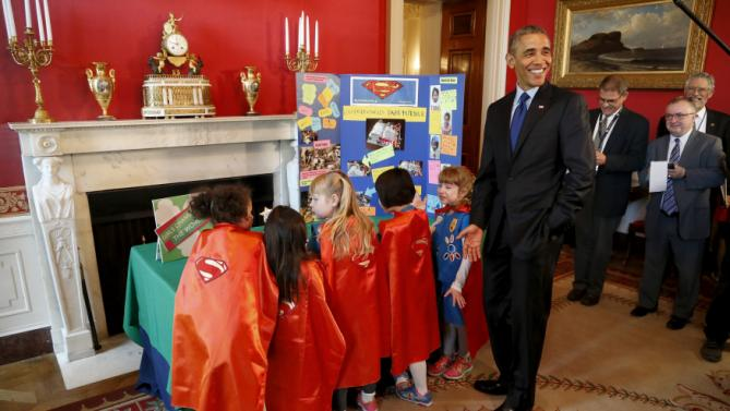 Obama reacts to a group of six-year-old Girl Scouts from Tulsa, Oklahoma, who made a battery-powered page turner, as he plays host to the 2015 White House Science Fair at the White House in Washington