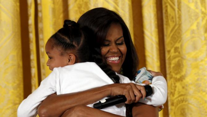 "Michelle Obama hugs Anaya during the White House's annual ""Take Our Sons and Daughters to Work Day"" in Washington"