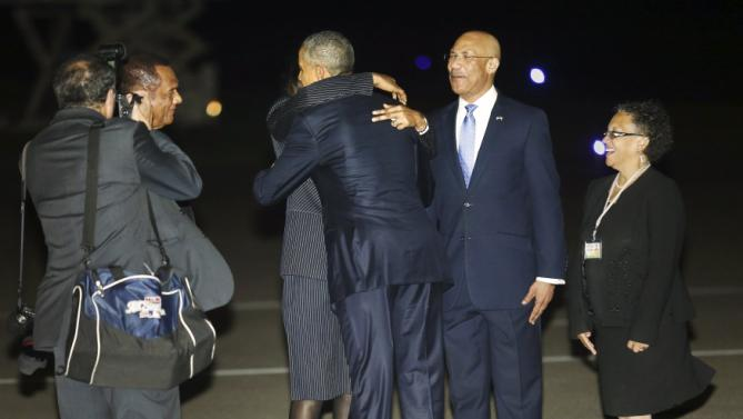 U.S. President Obama gets a hug from  from Jamaica's Prime Minister Simpson Miller as he arrives aboard Air Force One at Norman Manley International Airport in Kingston