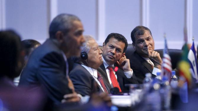 Correa smiles as he listens to remarks by Obama during the first plenary session of the Summit of the Americas in Panama City, Panama