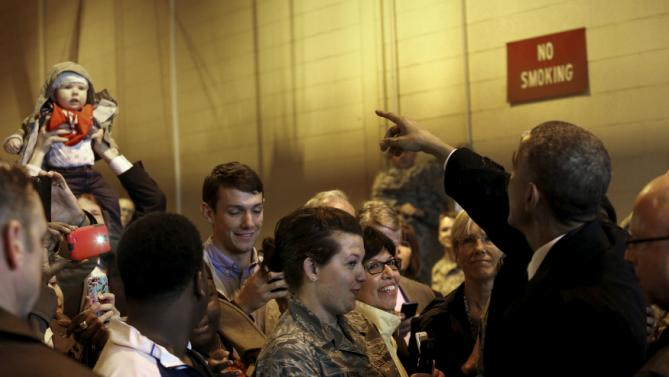 Obama says hello to a baby as he greets military families in a cargo bay after arriving aboard Air Force One at Charlotte Air National Guard Base in Charlotte, North Carolina