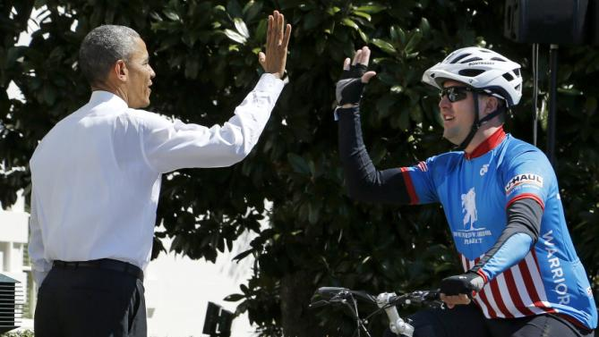 Obama cheers on a participant in the Wounded Warrior Project's Soldier Ride as they begin a 3-day ride to raise awareness for injured veterans with two laps around the South Lawn at the White House in Washington