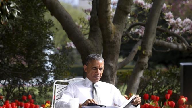 Obama reads papers at an outdoor table after signing the bill H.R. 2 Medicare Access and CHIP Reauthorization Act of 2015, the so-called Medicare 'doc fix,' in the Rose Garden at the White House in Washington