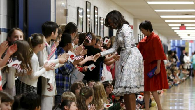 U.S. First Lady Michelle Obama and Mrs. Akie Abe, wife of Japanese Prime Minister Shinzo Abe, are greeted by students at Great Falls Elementary School