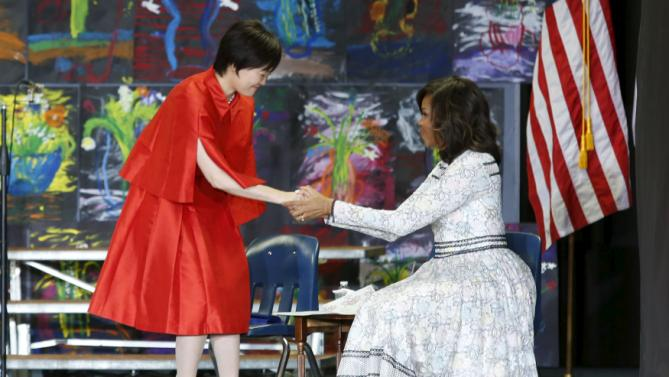 U.S. First Lady Michelle Obama greets Mrs. Akie Abe, wife of Japanese Prime Minister Shinzo Abe, at Great Falls Elementary School in Great Falls