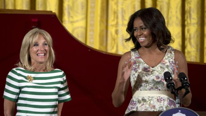 First lady Michelle Obama, right, joined by Jill Biden speaks to an audience of mothers and children during their annual Mother's Day Tea to honor military-connected mothers at the White House in Washington, Friday, May 8, 2015. (AP Photo/Carolyn Kaster)