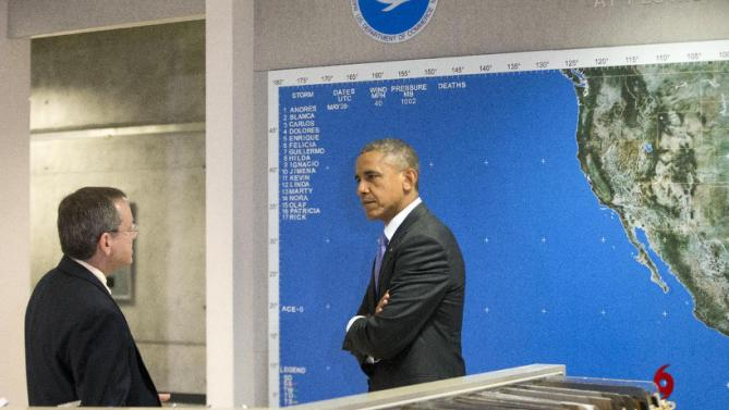 President Barack Obama listens to National Hurricane Center Director Rick Knabb during his tour of the National Hurricane Center in Miami, Thursday, May 28, 2015, to draw attention to preparedness in advance of the annual storm season that formally begins June 1. (AP Photo/Pablo Martinez Monsivais)