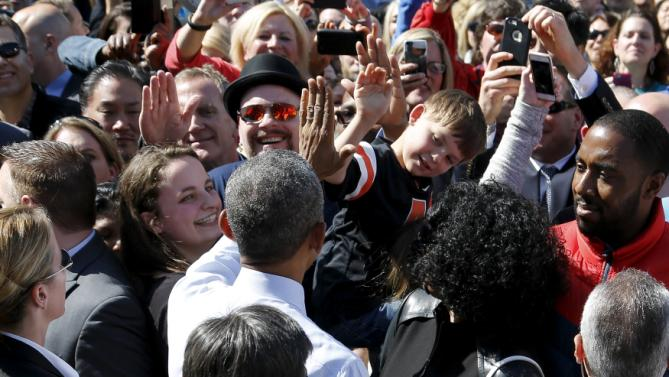 U.S. President Barack Obama high-fives a boy in the audience after his remarks on trade at Nike corporate headquarters in Beaverton, Oregon May 8, 2015. Obama on Friday pressed fellow Democrats to support his push for a trade deal with Asian countries, promoting the benefits he sees as attainable in a visit to sneaker maker Nike Inc, which promised the pact would help it create up to 10,000 U.S. jobs. REUTERS/Jonathan Ernst