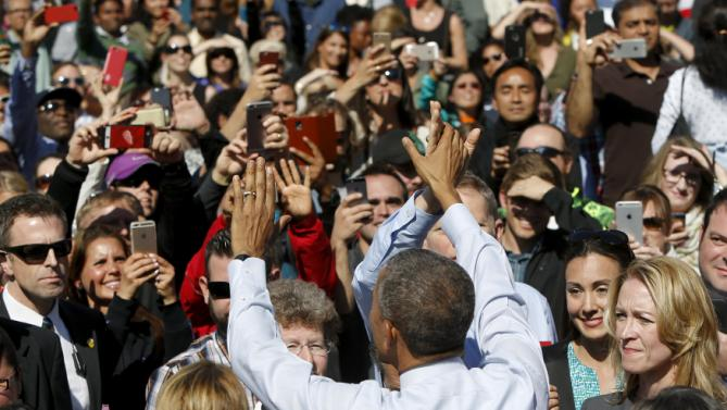 U.S. President Barack Obama high-fives employees after his remarks on trade at Nike corporate headquarters in Beaverton, Oregon May 8, 2015. Obama on Friday pressed fellow Democrats to support his push for a trade deal with Asian countries, promoting the benefits he sees as attainable in a visit to sneaker maker Nike Inc, which promised the pact would help it create up to 10,000 U.S. jobs. REUTERS/Jonathan Ernst