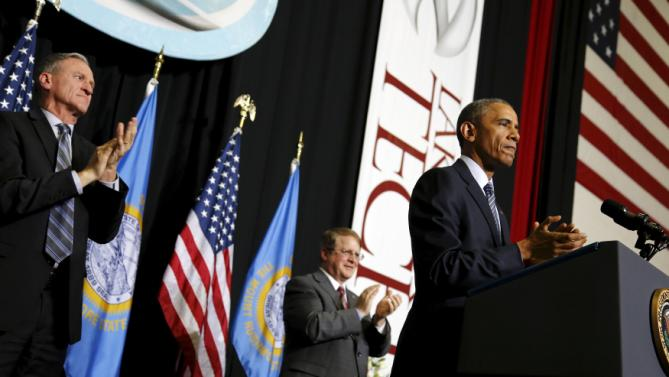 U.S. President Barack Obama applauds graduates during his commencement address to the graduating class at Lake Area Technical Institute in Watertown, South Dakota May 8, 2015. Also pictured are South Dakota Governor Dennis Daugaard (L) and Lake Area Technical Institute President Mike Cartney (2nd R). REUTERS/Jonathan Ernst