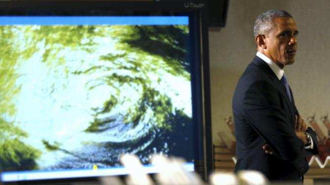 U.S. President Barack Obama passes an image of a hurricane during a tour of the National Hurricane Center in Miami, Florida, May 28, 2015. REUTERS/Kevin Lamarque