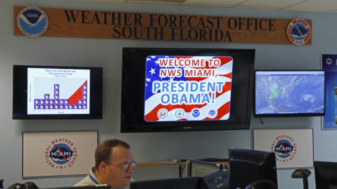A worker sits below a screen welcoming U.S. President Barack Obama during Obama's tour of the National Hurricane Center in Miami, Florida, May 28, 2015. REUTERS/Kevin Lamarque