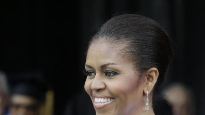 First lady Michelle Obama smiles after being hooded for an Honorary Degree of Doctor of Humanities from Oberlin College. Monday, May 25, 2015, in Oberlin, Ohio. (AP Photo/Tony Dejak)