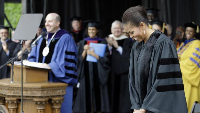 First lady Michelle Obama smiles as she is introduced by Oberlin College President Marvin Krislov before receiving an Honorary Degree of Doctor of Humanities from Oberlin College, Monday, May 25, 2015, in Oberlin, Ohio. (AP Photo/Tony Dejak)