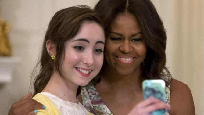 First lady Michelle Obama poses for a selfie with Hannah Bajakian during the annual Mother's Day Tea to honor military-connected mothers at the White House in Washington, Friday, May 8, 2015. Hannah's father, Todd Bajakian, leads the Warrior Transition Unit at Fort Drum, N.Y. (AP Photo/Carolyn Kaster)