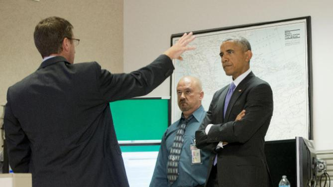 President Barack Obama listens during a tour of the National Hurricane Center in Miami, Thursday, May 28, 2015, to draw attention to preparedness in advance of the annual storm season that formally begins June 1. With Obama are National Hurricane Center Director Rick Knabb, left, and Hugh D. Cobb III, center, Chief, Tropical Analysis & Forecast Branch (AP Photo/Pablo Martinez Monsivais)
