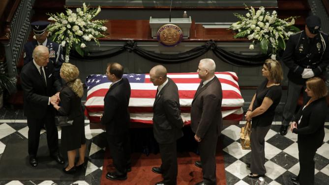 Vice President Joe Biden, left, greets mourners near a casket containing the remains of Biden's son, former Delaware Attorney General Beau Biden, during a viewing, Thursday, June 4, 2015, at Legislative Hall in Dover, Del. Beau Biden died of brain cancer Saturday at age 46. (AP Photo/Patrick Semansky, Pool)