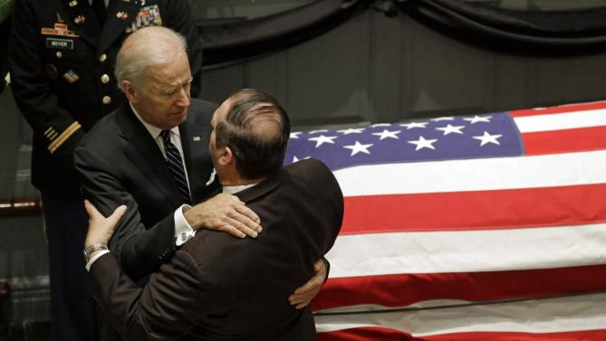 Vice President Joe Biden, left, hugs a mourner as they stand near a casket containing the remains of Biden's son, former Delaware Attorney General Beau Biden, during a viewing, Thursday, June 4, 2015, at Legislative Hall in Dover, Del. Beau Biden died of brain cancer Saturday at age 46. (AP Photo/Patrick Semansky)