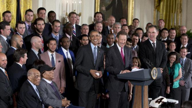 President Barack Obama, joined by, from left, San Francisco  Giants Hall of Fame baseball players Monte Irvin and Willie Mays, Giants CEO Larry Baer, and team manager Bruce Bochy, holds an autographed baseball given to him by San Francisco Giants pitcher Madison Bumgarner during a ceremony in the East Room of the White House in Washington, Thursday, June 4, 2015, where the president honored the team and their 2014 World Series baseball victory. (AP Photo/Carolyn Kaster)