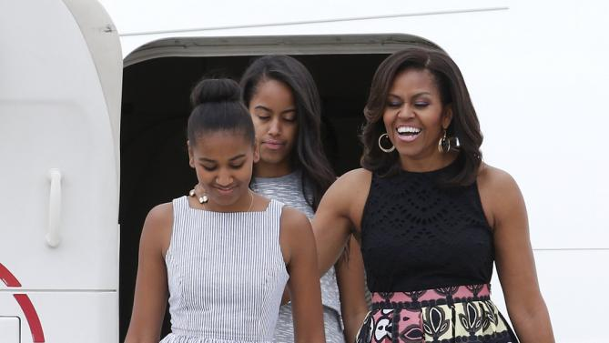 U.S. first lady Michelle Obama (R) arrives with her daughter Sasha (L) and Malia at Malpensa airport in Milan, Italy, as part of her European trip June 17, 2015.  REUTERS/Alessandro Garofalo