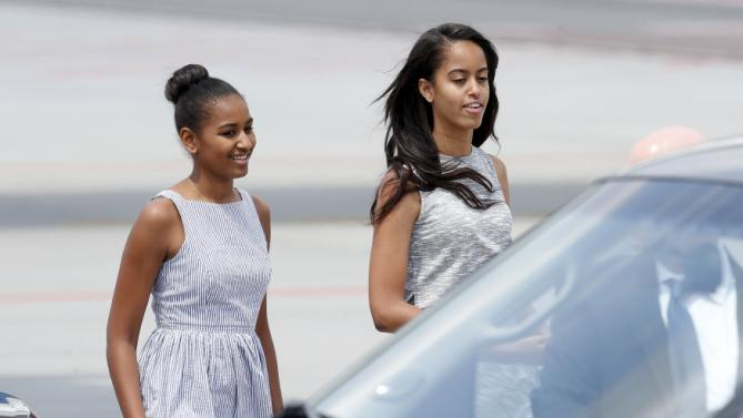 U.S. first lady Michelle Obama's daughters Sasha (L) and Malia walk as they arrive at Malpensa airport in Milan, Italy, as part of her European trip June 17, 2015.  REUTERS/Alessandro Garofalo