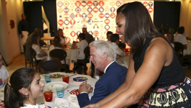 U.S. first lady Michelle Obama greets a child at James Beard American Restaurant, as part of her European trip, in Milan, Italy, June 17, 2015.  REUTERS/Stefano Rellandini