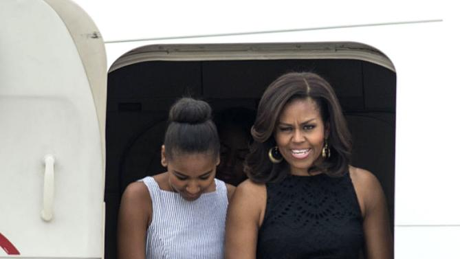 U.S. first lady Michelle Obama, right, and her daughter Sasha disembark from a plane as they arrive at Malpensa airport in Milan, Italy, Wednesday, June 17, 2015. Michelle Obama has arrived in Milan on the second leg of a European trip that puts an international spin on her core initiatives. (AP Photo/Giuseppe Aresu)