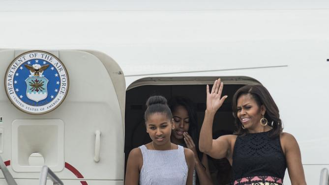 U.S. first lady Michelle Obama, right, her daughters Sasha, left, and Malia disembark from a plane as they arrive at Malpensa airport in Milan, Italy, Wednesday, June 17, 2015. Michelle Obama has arrived in Milan on the second leg of a European trip that puts an international spin on her core initiatives. (AP Photo/Giuseppe Aresu)