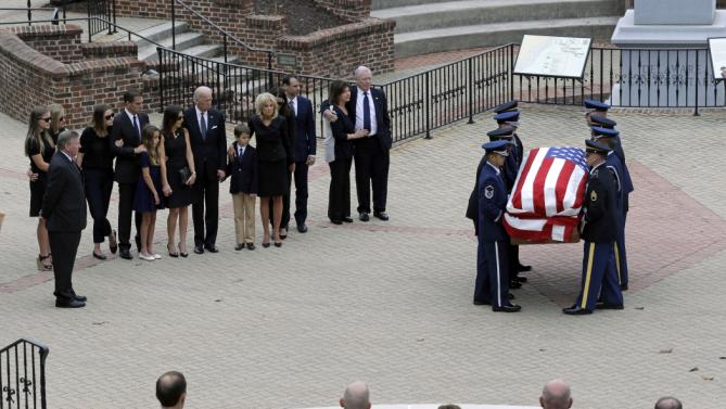 An honor guard carries a casket containing the remains of former Delaware Attorney General Beau Biden as members of the Biden family, left, look on, Thursday, June 4, 2015, before a viewing at Legislative Hall in Dover, Del. Biden, the vice president's eldest son, died of brain cancer Saturday at age 46. (AP Photo/Patrick Semansky)