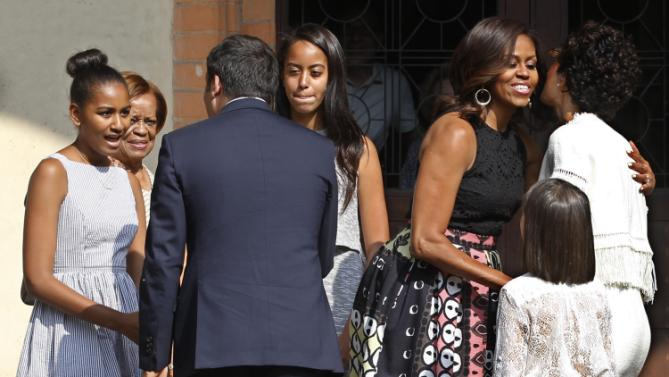 "U.S. first lady Michelle Obama embraces Agnese Landini, wife of Italian premier Matteo Renzi, while he greets her daughters Sasha, left, and Malia, as she arrives at the Santa Maria delle Grazie church to see Leonardo's masterpiece ""The Last Supper"", after participating in a cooking demonstration at the James Beard American Restaurant with Italian and American middle school students in Milan, Italy, Wednesday, June 17, 2015.  Behind is Mrs Obama mother Marian Robinson. Michelle Obama is in Milan on the second leg of a European trip that puts an international spin on her core initiatives. (AP Photo/Antonio Calanni)"