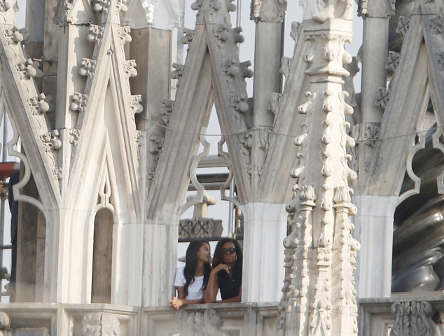 U.S. first lady Michelle Obama and her daughter Malia watch the panorama from the roof of the Duomo gothic cathedral in Milan, Italy, Thursday, June 18, 2015. Earlier Michelle Obama  toured the U.S. and Italian pavilions at the Expo 2015 world's fair focused on food and nutrition, topics in step with the first lady's initiative to promote healthy eating. (AP Photo/Luca Bruno)