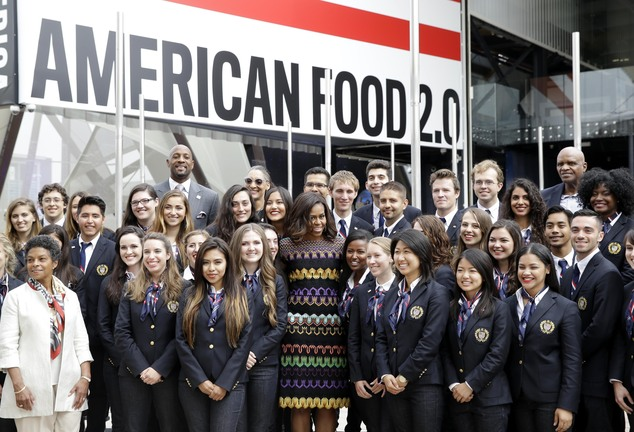 """U.S. first lady Michelle Obama, center, poses for a photo with workers of the United States pavilion at the 2015 Expo in Rho, near Milan, Italy, Thursday, June 18, 2015. Mrs. Obama is leading a presidential delegation Thursday to the world's fair, organized around issues concerning food and nutrition, which dovetails with the U.S. first lady's """"Let's Move"""" initiative to fight childhood obesity through diet and exercise. (AP Photo/Antonio Calanni)"""