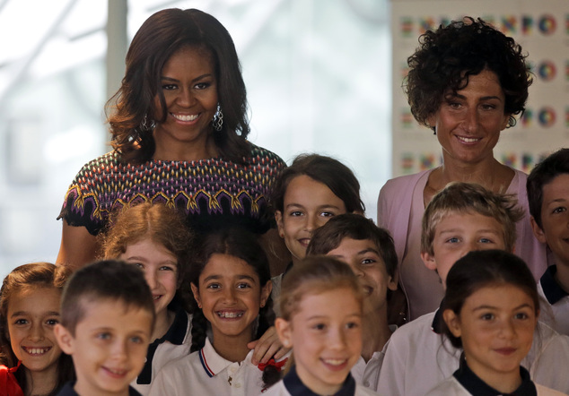 """U.S. first lady Michelle Obama, left, flanked by Italy's first lady Agnese Landini, meets Italian schoolchildren during her visit at the Italian pavilion at the 2015 Expo in Rho, near Milan, Italy, Thursday, June 18, 2015. Mrs. Obama is leading a presidential delegation Thursday to the world's fair, organized around issues concerning food and nutrition, which dovetails with the U.S. first lady's """"Let's Move"""" initiative to fight childhood obesity through diet and exercise. (AP Photo/Antonio Calanni)"""