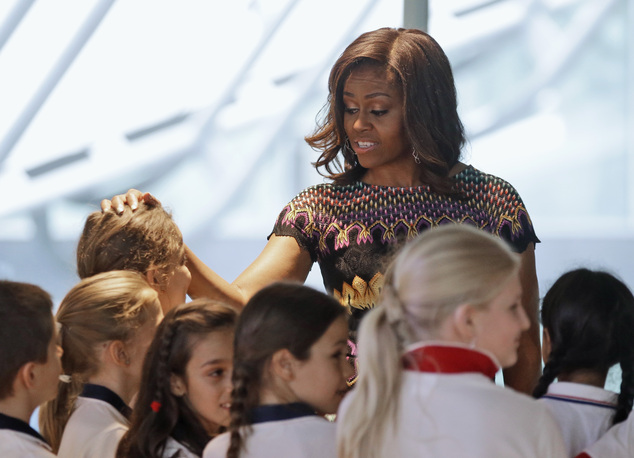 """U.S. first lady Michelle Obama meets Italian schoolchildren during her visit at the Italian pavilion at the 2015 Expo in Rho, near Milan, Italy, Thursday, June 18, 2015. Mrs. Obama is leading a presidential delegation Thursday to the world's fair, organized around issues concerning food and nutrition, which dovetails with the U.S. first lady's """"Let's Move"""" initiative to fight childhood obesity through diet and exercise. (AP Photo/Antonio Calanni)"""