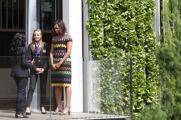 """U.S. first lady Michelle Obama, right, visits the United States pavilion at the 2015 Expo in Rho, near Milan, Italy, Thursday, June 18, 2015. Mrs. Obama is leading a presidential delegation Thursday to the world's fair, organized around issues concerning food and nutrition, which dovetails with the U.S. first lady's """"Let's Move"""" initiative to fight childhood obesity through diet and exercise. (AP Photo/Antonio Calanni)"""