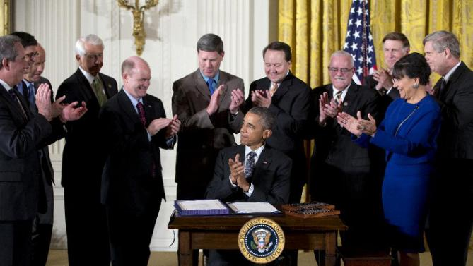 Surrounded by Cabinet officials and members of Congress, President Barack Obama applauds after signing H.R. 2146 Defending Public Safety Employees' Retirement Act and H.R. 1295 Trade Preferences Extension Act of 2015 , Monday, June 29, 2015, in the East Room of the White House in Washington. From left are, U.S. Trade Representative Michael Froman, Treasury Secretary Jacob Lew, Rep. John Delaney, D- Md., Rep. David Reichert, R-Wash., Sen.. Chris Coons, D-Del., Rep. Ron Kind, D- Wis., Rep. Pat Tiberi, R-Ohio, Rep. Gerald Connolly, D-Va., Rep. Donald Beyer, D-Va., Commerce Secretary Penny Pritzker, and Agriculture Secretary Tom Vilsack. (AP Photo/Carolyn Kaster)