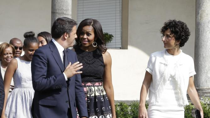 "U.S. first lady Michelle Obama talks with Italian premier Matteo Renzi as she arrives at the Santa Maria delle Grazie church to see Leonardo's masterpiece ""The Last Supper"", after participating in a cooking demonstration at the James Beard American Restaurant with Italian and American middle school students in Milan, Italy, Wednesday, June 17, 2015.  At right is Renzi's wife Agnes, while behind are Michelle's daughters Malia and Sasha and her mother Marian Robinson. Michelle Obama is in Milan on the second leg of a European trip that puts an international spin on her core initiatives. (AP Photo/Antonio Calanni)"