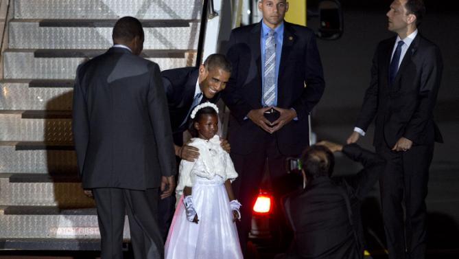 U.S. President Barack Obama poses for a photograph with a girl who gave him flowers on his arrival at the Jomo Kenyatta International Airport in Nairobi, Kenya, Friday, July 24, 2015. Obama began his first visit to Kenya as U.S. president Friday. (AP Photo/Ben Curtis)