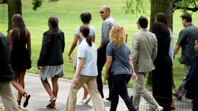 President Barack Obama, center top, accompanied by his daughter, Sasha, at his left, friends, family, and secret service agents, walks through Central Park, Saturday, July 18, 2015, in New York. Obama is spending a mainly personal weekend with his daughters in New York City. (AP Photo/Andrew Harnik)