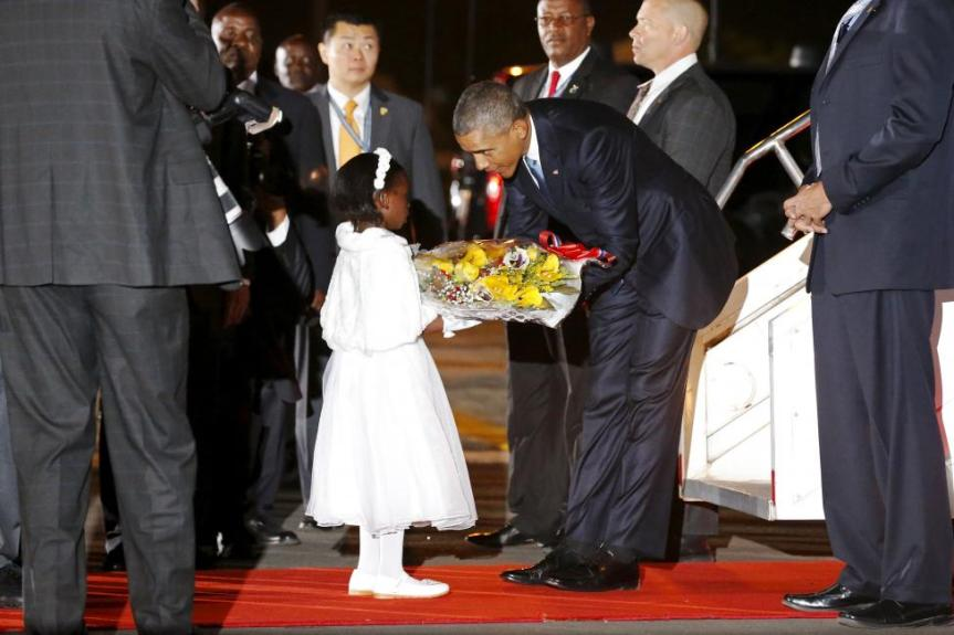 Obama receives flowers from a young girl as he arrives aboard Air Force One at Jomo Kenyatta International Airport in Nairobi
