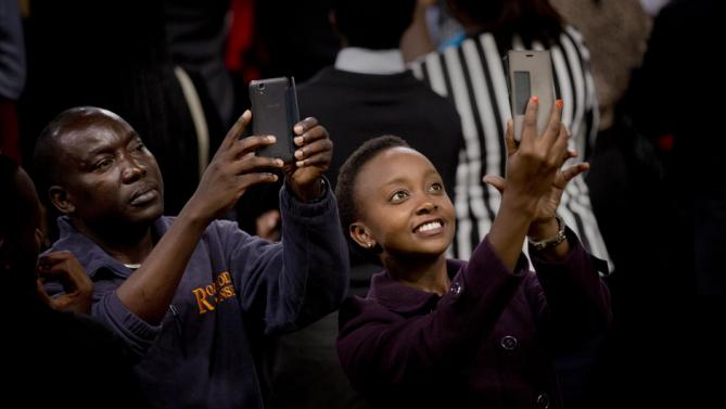 Members of the audience take selfies as President Barack Obama gives a speech behind them, at the Safaricom Indoor Arena in the Kasarani area of Nairobi, Kenya Sunday, July 26, 2015. Obama is traveling on a two-nation African tour where he will become the first sitting U.S. president to visit Kenya and Ethiopia. (AP Photo/Ben Curtis)