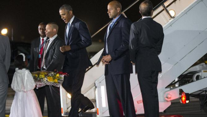Eight year-old Joan Wamaitha greets President Barack Obama with flowers as he arrives at Kenyatta International Airport, on Friday, July 24, 2015, in Nairobi, Kenya. Obama's link to Kenya, where he began his first visit as U.S. president Friday, is a father he barely knew but whose influence can nonetheless be seen in his son's presidency. (AP Photo/Evan Vucci)