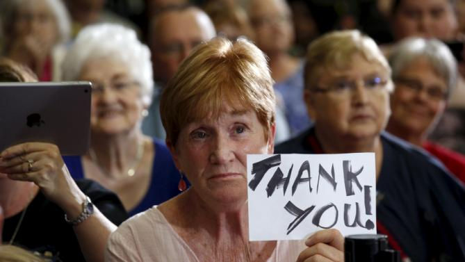 A woman holds up a sign as U.S. President Barack Obama speaks about the economy during a visit to the University of Wisconsin La Crosse in La Crosse, Wisconsin July 2, 2015. REUTERS/Kevin Lamarque